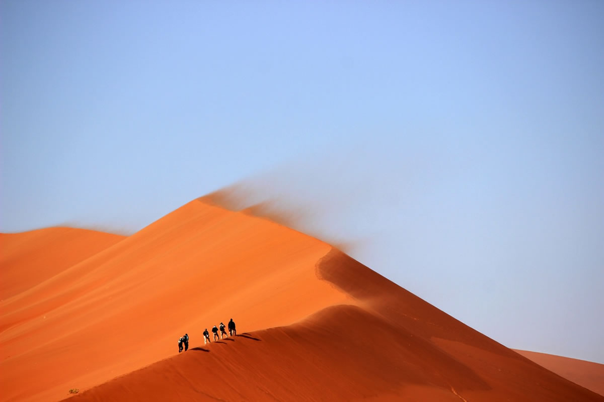 People walking up the sand dunes